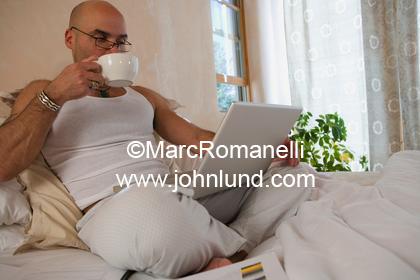 Man having his coffee in bed in the morning and looking at his laptop. He is dressed casual in all white. He is bald.